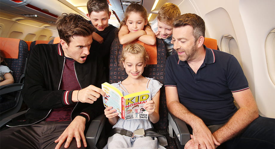 Greg James and Chris Smith with children, reading books on a plane.
